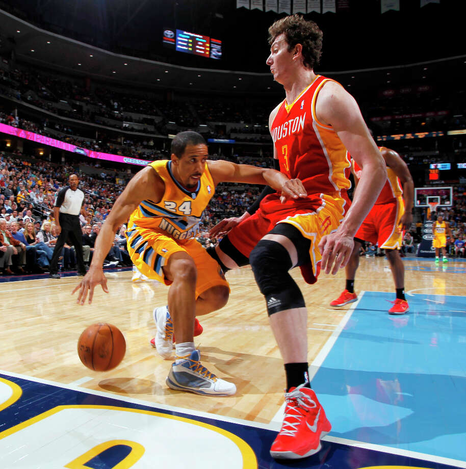 Nuggets guard Andre Miller is stopped on a drive by Rockets center Omer Asik. Photo: David Zalubowski