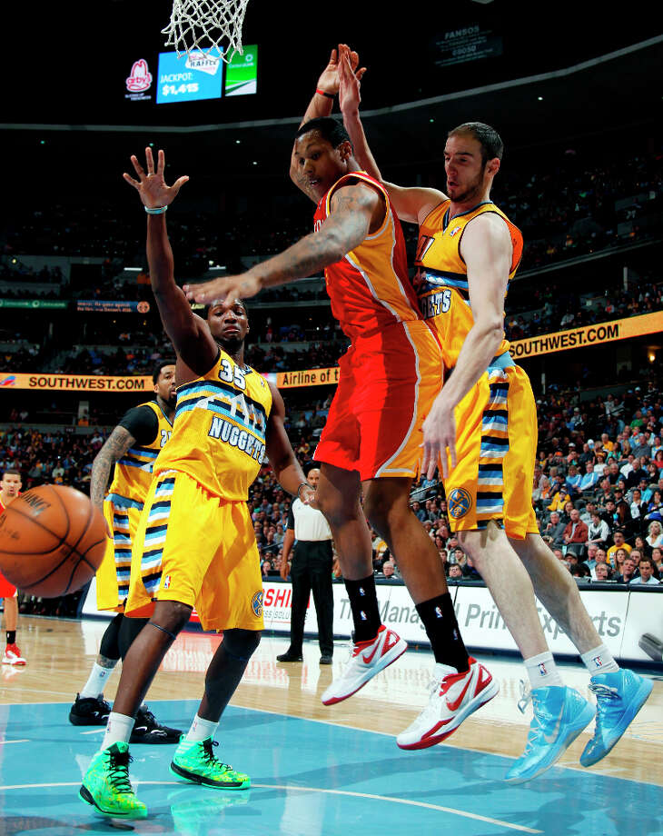 Rockets center Greg Smith loses control while driving to the basket as Kenneth Faried and Kosta Koufos of the Nuggets defend. Photo: David Zalubowski