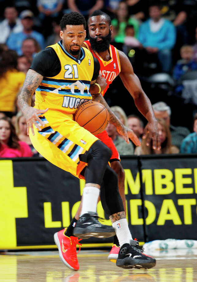 Wilson Chandler of the Nuggets tries to contain a loose ball while Rockets guard James Harden defends. Photo: David Zalubowski, Associated Press