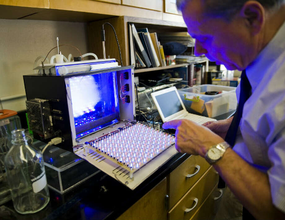 University of Texas professor Jerry Brand opens a device that uses light to aid in the growth of algae in the school's biology building. Photo: Ashley Landis, Houston Chronicle