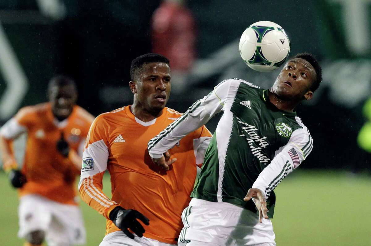 Portland Timbers forward Rodney Wallace, right, works to trap a fly ball as Houston Dynamo defender Jermaine Taylor watches during the second half of an MLS soccer game in Portland, Ore., Saturday, April 6, 2013. Portland won 2-0. (AP Photo/Don Ryan)