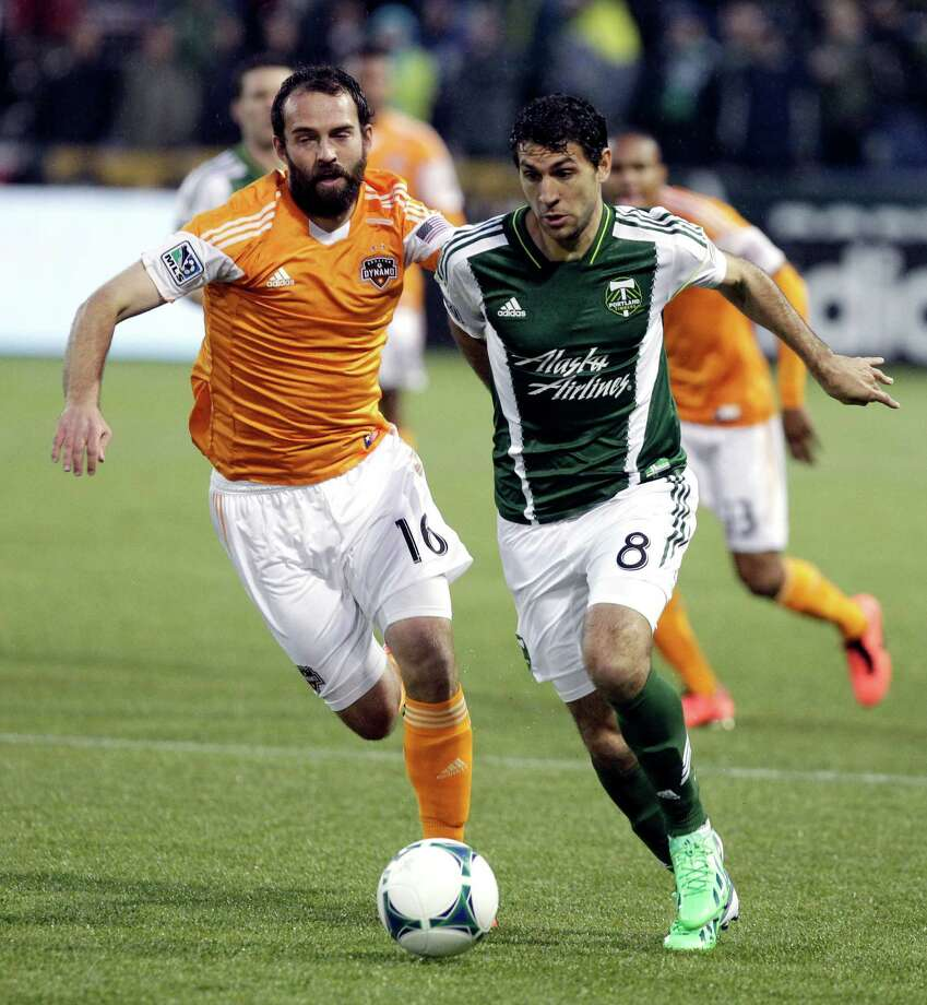 Portland Timbers midfielder Diego Valeri, right, and Houston Dynamo midfielder Adam Moffat chase down the ball during the first half of an MLS soccer game in Portland, Ore., Saturday, April 6, 2013. (AP Photo/Don Ryan) Photo: Don Ryan, Associated Press / AP