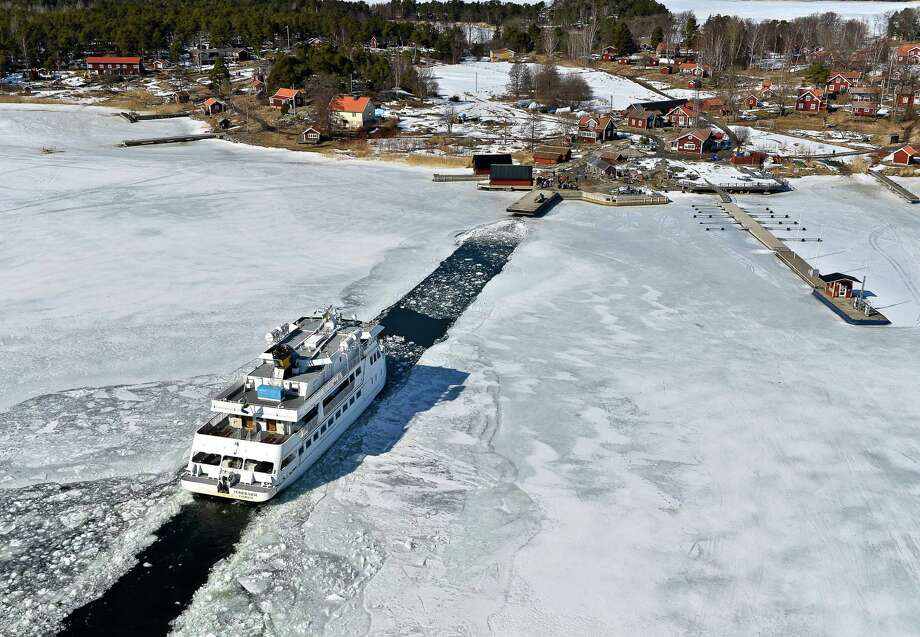 The passenger ship 'Soderarm' heads Friday morning April 5, 2013, in a channel through the ice made by an icebreaker, for the jetty of the island Husaro in the Stockholm archipelago in Sweden. According to Swedish Metereological and Hydrological Institute (SMHI), the ice coverage in the Baltic is the thickest and most extensive ever on record. (AP photo / Scanpix Sweden / Anders Wiklund) Photo: AP