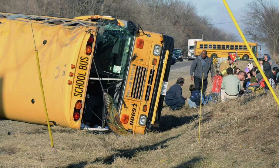 Rescue personnel attend to children from Newport Elementary School after their school bus overturned Friday, April 5, 2015, near Wadsworth, Ill. There were about two dozen children on board. There was no immediate word on injuries. (AP Photo/Lake County News-Sun, Thomas Delany Jr.) Photo: AP