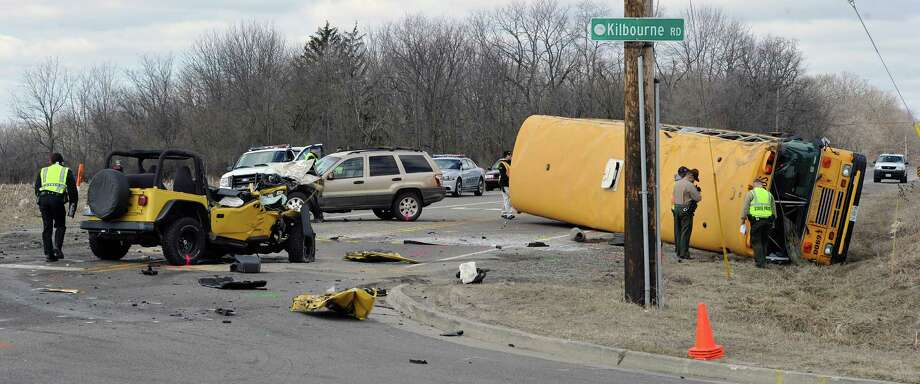 Investigators gather evidence from the scene of a three vehicle accident, including a school bus where the driver of a Jeep Wrangler was killed on Friday, April 5, 2013, near Wadsworth, Ill.  Over two dozen school children were on the bus, most receiving minor injuries. Photo: AP
