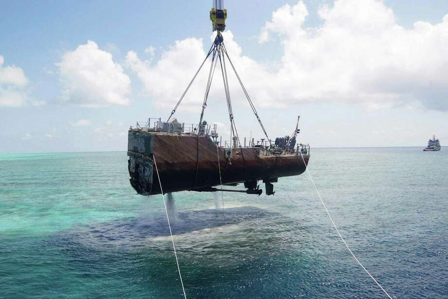 In this March 30, 2013 photo released by the Philippine Coast Guard on Monday, April 1, 2013, the stern of the USS Guardian, a U.S. minesweeper, is lifted out of water at the Tubbataha Reef, a World Heritage site, southwest of the Philippines. Tubbataha Reef park superintendent Angelique Songco said the fine for damaging the protected coral reef would be about 24,000 pesos ($600) per square meter, so the U.S. could be facing a fine of more than $2 million. Photo: AP