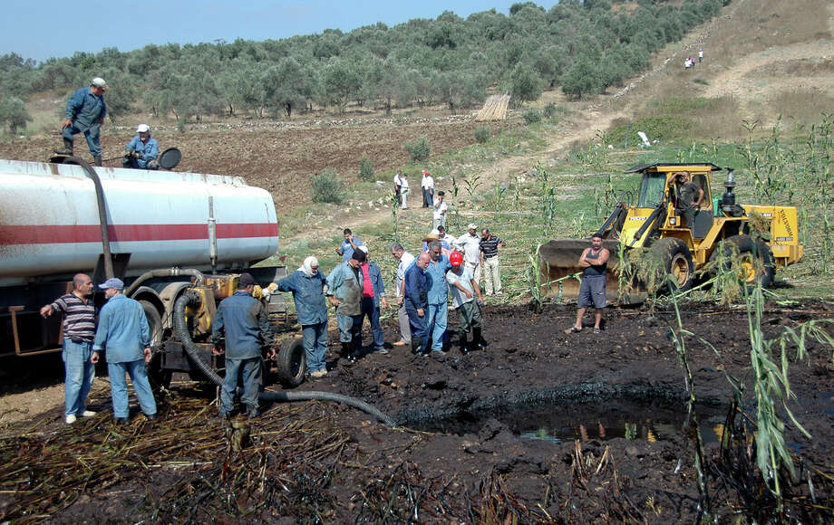 This Friday, July 29, 2011 file photo released by the Syrian official news agency SANA, shows workers pumping oil from the site of a bomb blast that struck a major oil pipeline in the western town of Talkalakh, Syria. Syria's vital oil industry is breaking down as rebels capture many of the country's oil fields, with wells aflame and looters scooping up crude, depriving the government of much needed cash and fuel for its war machine against the uprising. Photo: AP