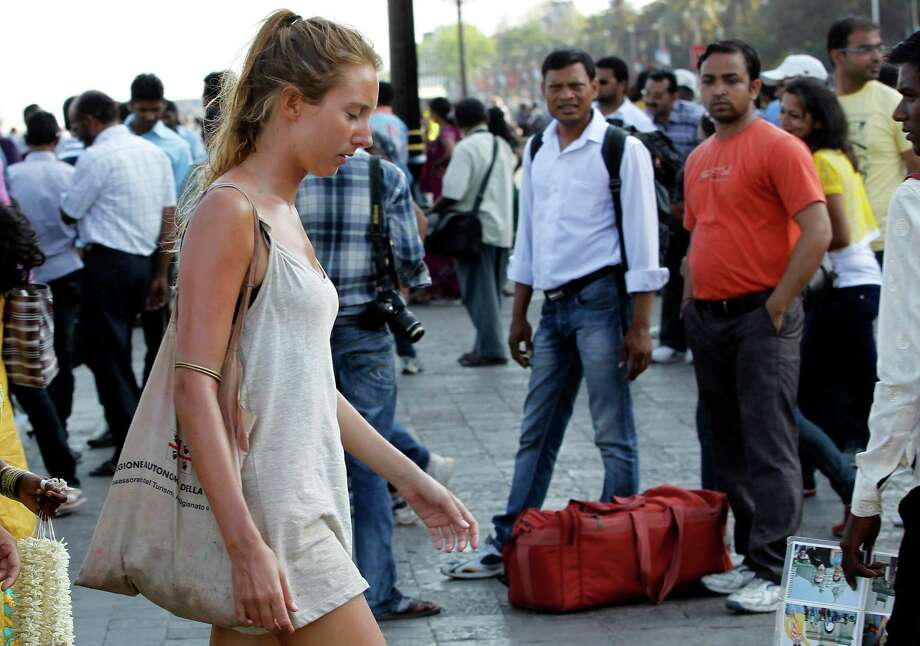 In this Tuesday, April 2, 2013 photo, German tourist Carolina De Paola, 22, walks near the landmark Gateway of India in Mumbai, India. A fatal gang rape in New Delhi didn't deter Germans De Paolo and Canan Wahner from traveling to India for a six-week tour. On a train, a man grabbed De Paolo's breasts from behind but she never reported the crime, deciding there would be no point. Violence against women, and the huge publicity generated by recent attacks here, is threatening India's $17.7 billion tourism industry with a new study showing tourism has plunged. Photo: AP