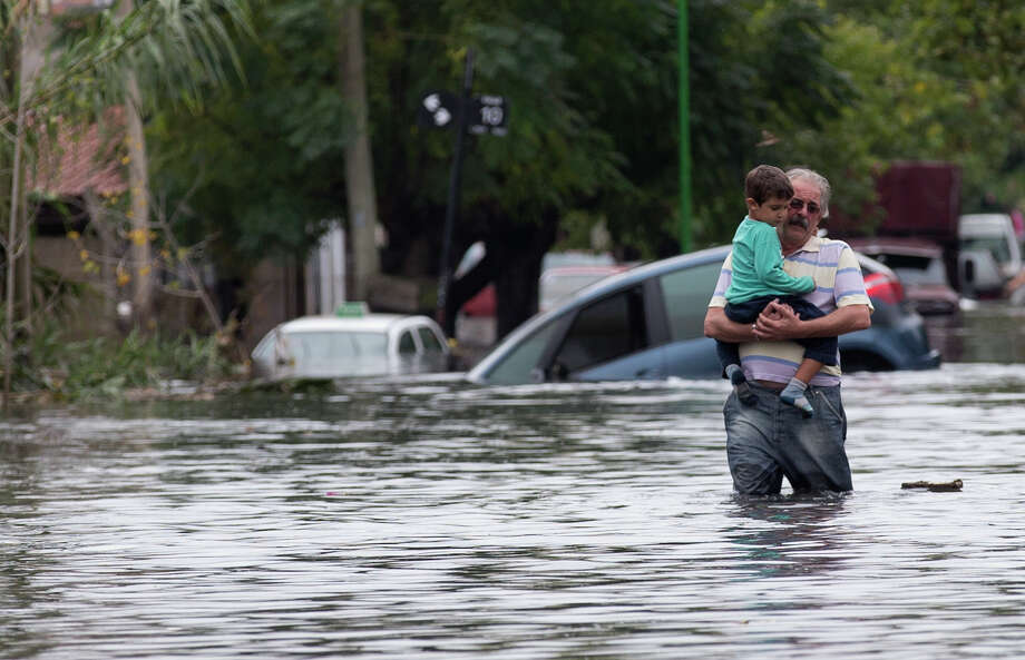 A man with a boy in his arms wades through a flooded street in La Plata, in Argentina's Buenos Aires province, Wednesday, April 3, 2013. At least 35 people were killed by flooding overnight in Argentina's Buenos Aires province, the governor said Wednesday, bringing the overall death toll from days of torrential rains to at least 41 and leaving large stretches of the provincial capital under water. Photo: AP