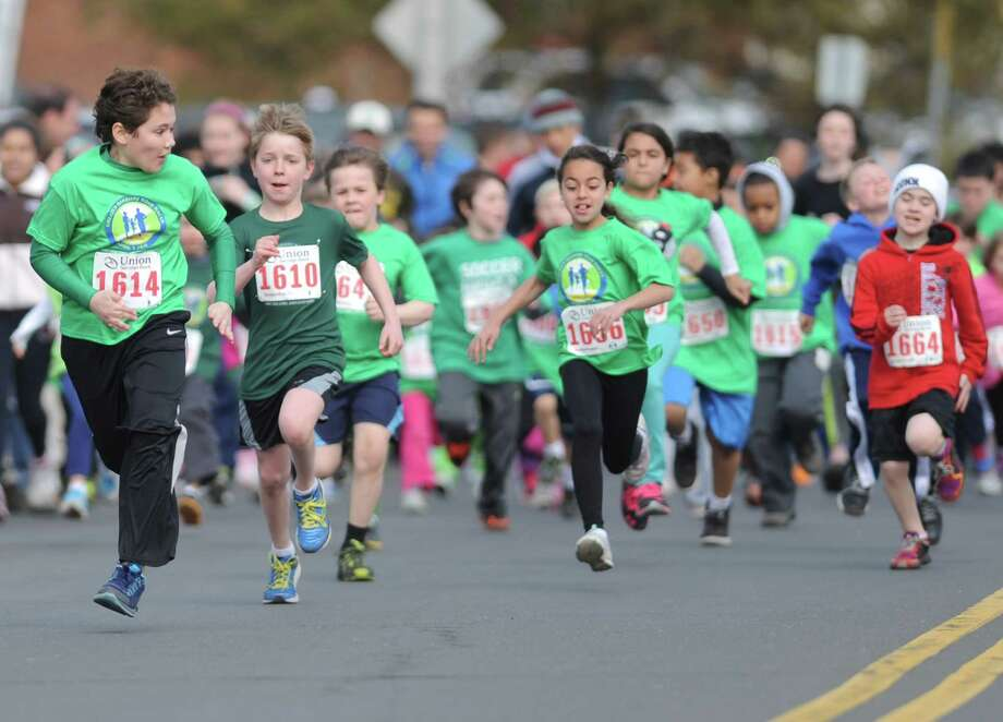 Jaden Cazorla, 10, of Danbury, leads the pack at the start of the Union Savings Bank Kids Run at the Stratton Faxon Greater Danbury Half-Marathon and 5K road races at Rogers Park in Danbury, Conn. on Sunday, April 7, 2013.  Kataline Baehing, 11, of Hamden was the winner of the kids run. Photo: Tyler Sizemore / The News-Times