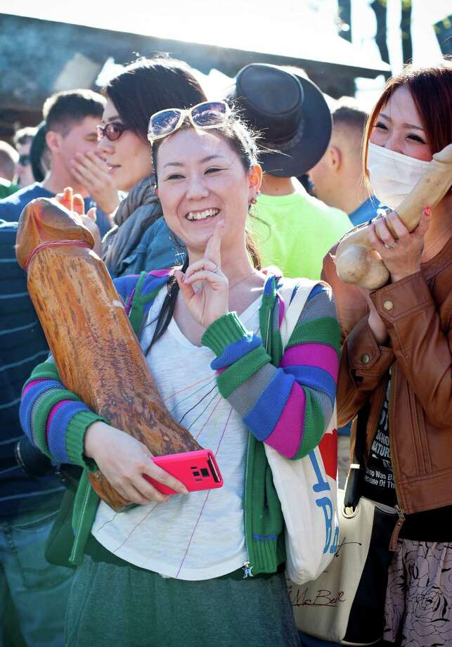 People enjoy taking photos with wooden phallic-shaped statue at Kanamara Matsuri (Festival of the Steel Phallus) on April 7, 2013 in Kawasaki, Japan. The festival is held annually on the first Sunday of April and it is centered around a local penis-venerating shrine once popular among prostitutes who wished to pray for protection from sexually transmitted diseases. The festival is now a popular tourist attraction. Photo: Keith Tsuji, Getty / 2013 Getty Images