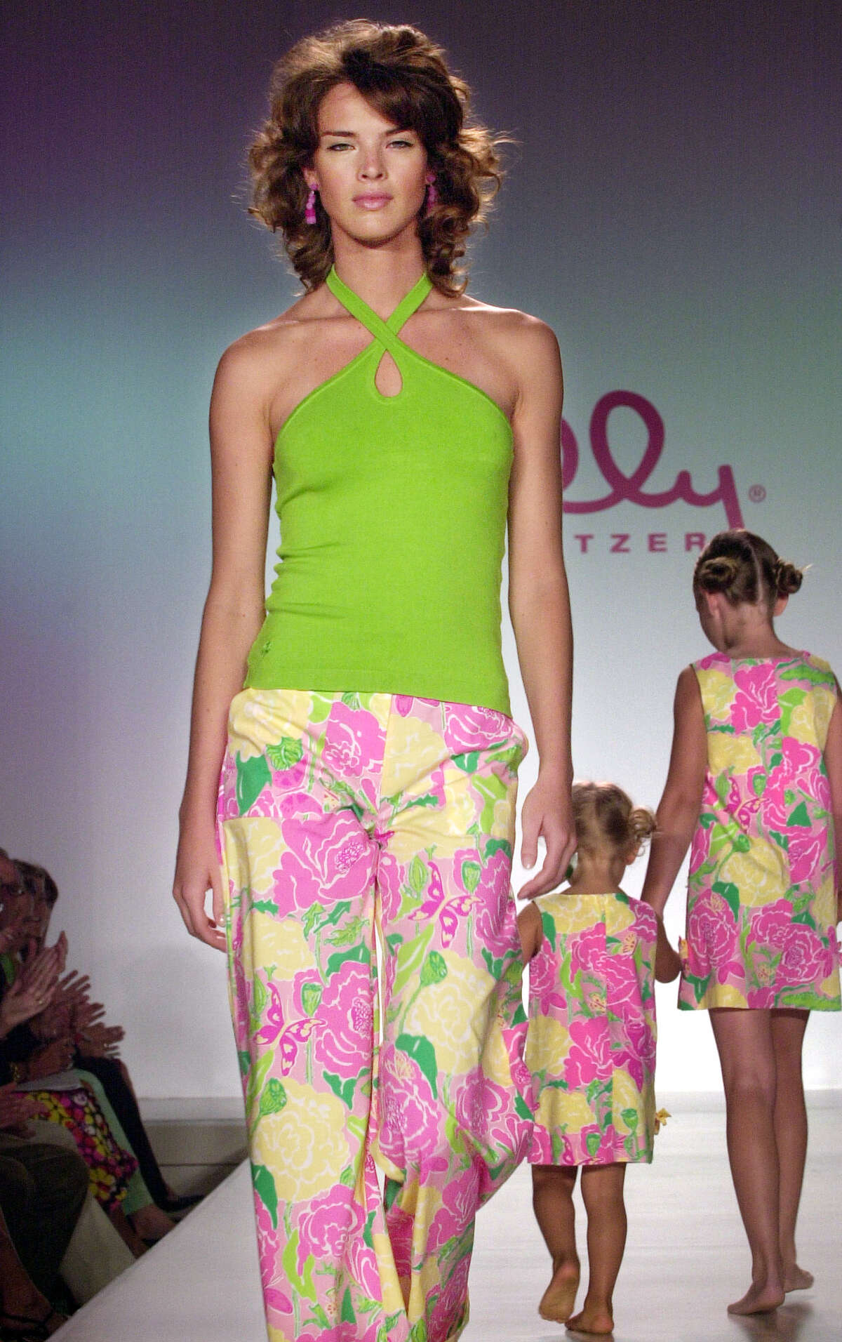 A model wears a shoofly jesse pants and everglade green jaime halter, while child models wear shoofly lilly dresses during the showing of Lilly Pulitzer spring 2003 fashions in New York, Saturday Sept. 21, 2002.