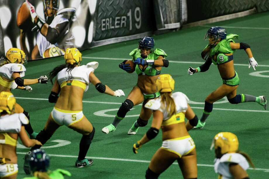 The Mist's Shuree Hyatt, center, charges into a pack of Green Bay Chill defense during a lingerie football game Saturday, April 6, 2013, at the ShoWare Center in Kent. Photo: JORDAN STEAD / SEATTLEPI.COM