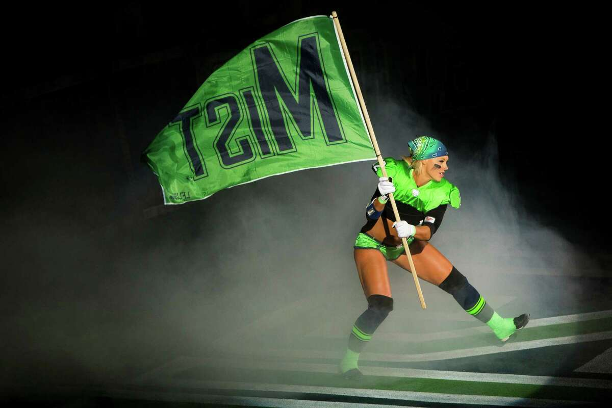 Seattle Mist player Christine Moore hypes up the crowd during the introduction of her teammates at the beginning of a lingerie football game against the Green Bay Chill Saturday, April 6, 2013, at the ShoWare Center in Kent.