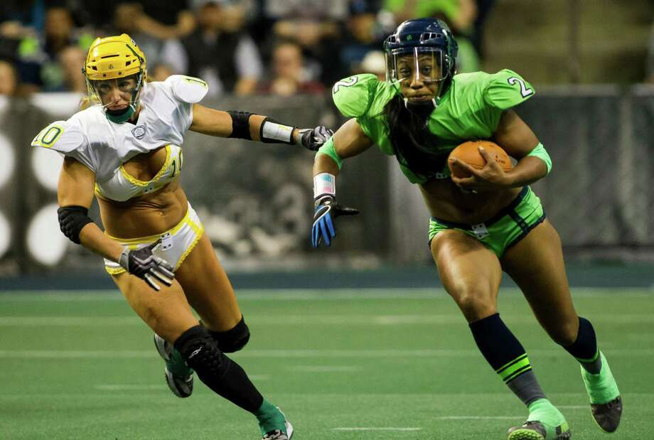 Seattle Mist running back Mele Rich, right, charges downfield during a lingerie football game against the Green Bay Chill Saturday, April 6, 2013, at the ShoWare Center in Kent. Photo: JORDAN STEAD / SEATTLEPI.COM