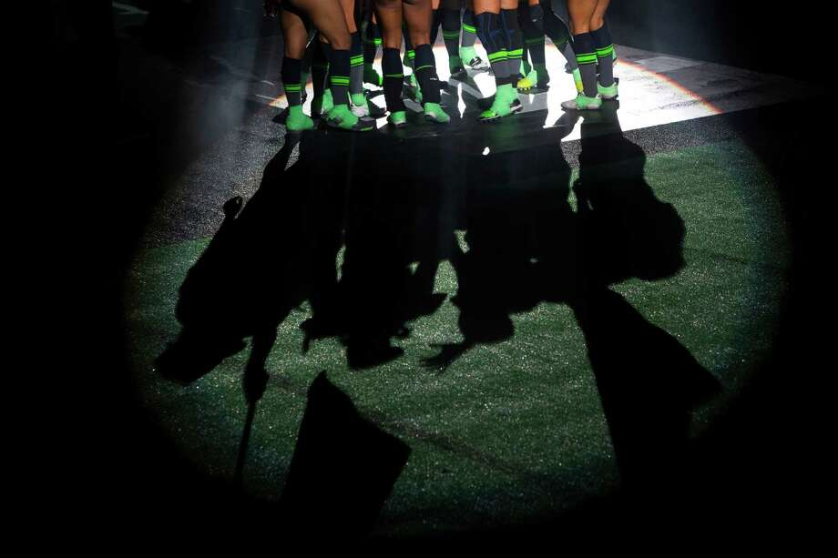 Seattle Mist players huddle in the spotlight after taking to the field for a lingerie football game against the Green Bay Chill Saturday, April 6, 2013, at the ShoWare Center in Kent. Photo: JORDAN STEAD / SEATTLEPI.COM
