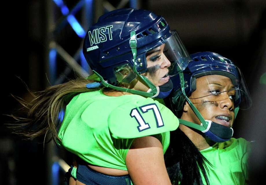 Following a touchdown for her team, Seattle Mist player Megan Hanson, left, rejoices with a teammate during a lingerie football game against the Green Bay Chill Saturday, April 6, 2013, at the ShoWare Center in Kent. Photo: JORDAN STEAD / SEATTLEPI.COM