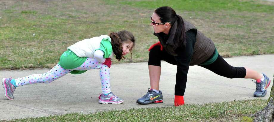 Ava Kijewski, 6, and her mom, Regina, strech before the Stratton Faxon Greater Danbury Half Marathon and 5K race in Danbury, Conn. Sunday, April 7, 2013. Photo: Michael Duffy / The News-Times