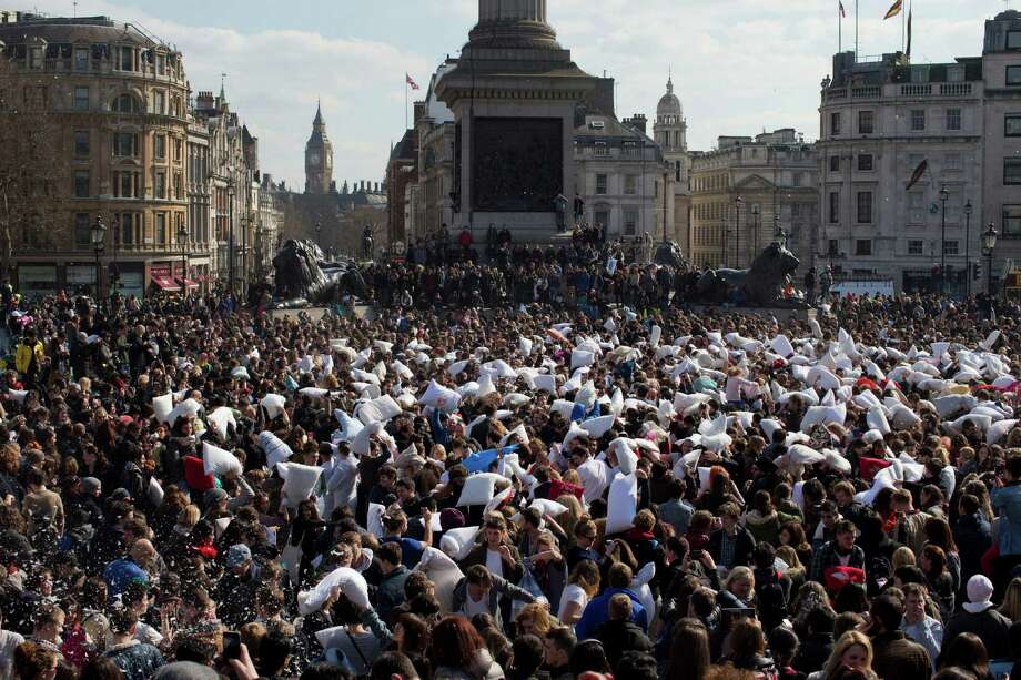 "People take part in a pillow fight in Trafalgar Square, as the ""Big Ben"" Elizabeth Tower of the Houses of Parliament is seen in the distance, in London, Saturday, April 6, 2013.  A coordinated set of pillow fights took place in cities around the world on Saturday.  The organizers of the London event stated, there are only two rules, don't hit anyone with a camera and don't hit anyone without a pillow. Photo: AP"