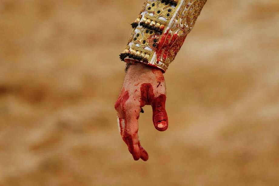 Spain's bullfighter Juan Jose Padilla's hand is stained with blood from a bull during a bullfight at La Muralla bullring in Brihuega, Spain, Saturday, April 6, 2013. Bullfighting is an ancient tradition in Spain and the season runs from March to October. Photo: AP