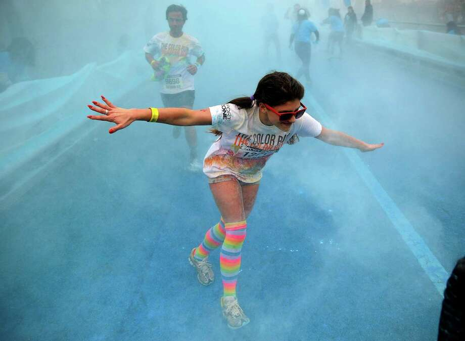 Runners are coated in powder as they make their way through the blue station during The Color Run in Matosinhos, Portugal, Sunday, April 7, 2013.  The Color Run is a 5K feel good, happy event where participants run through different color stations, were are splashed with colored powder, and then partied at the finish line in clouds of multicolored fun. Photo: AP