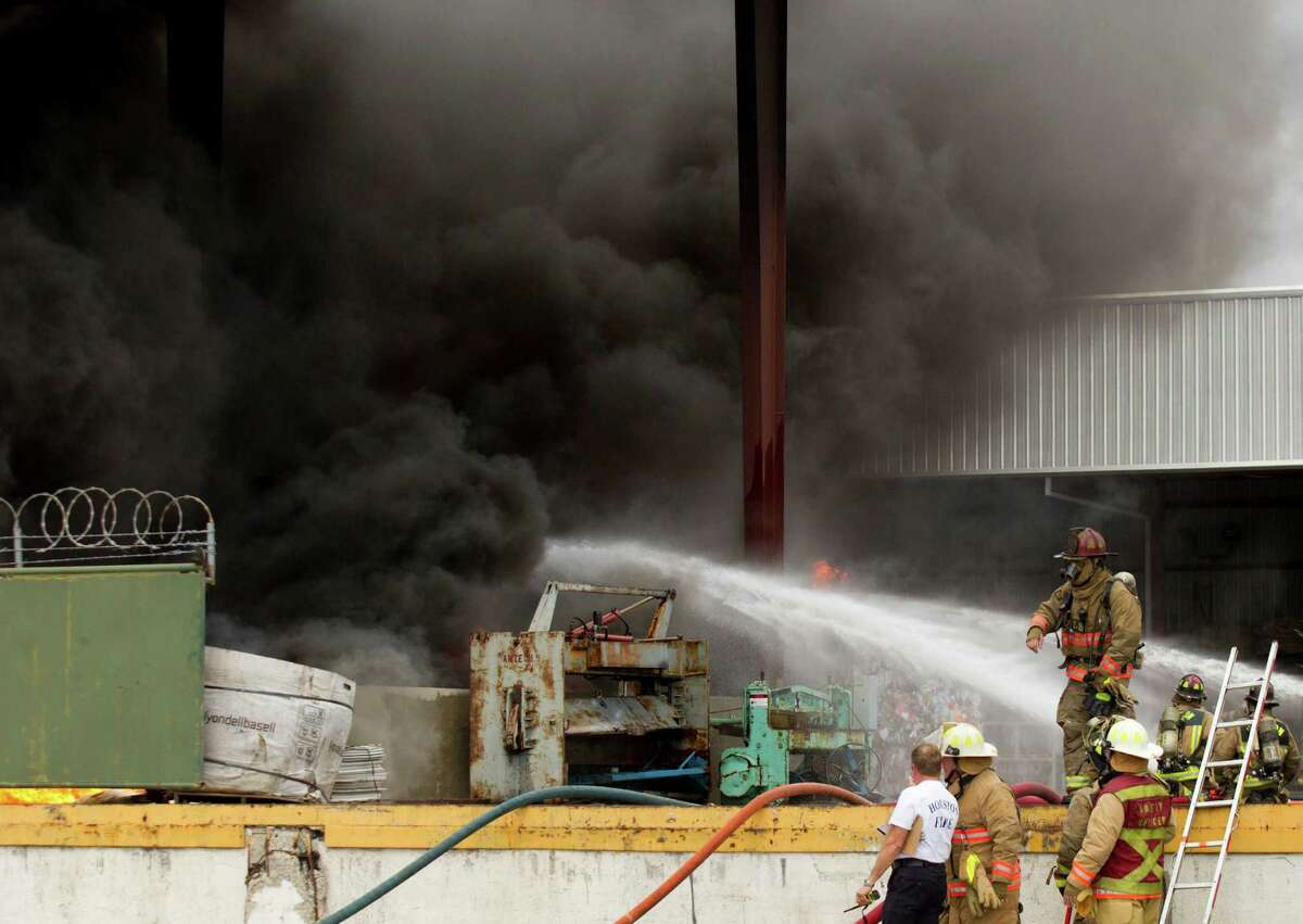Houston firefighters battle a blaze at a recycling plant near the intersection of Old Clinton Road and Kress Sunday, April 7, 2013, in Houston.