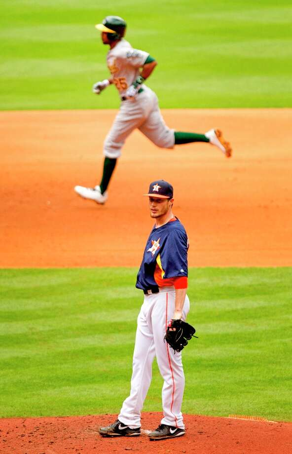 Athletics outfielder Chris Young (25) rounds the bases after hitting a three-run home run off of Astros starting pitcher Lucas Harrell, bottom, during the fifth inning. Photo: Brett Coomer / © 2013 Houston Chronicle