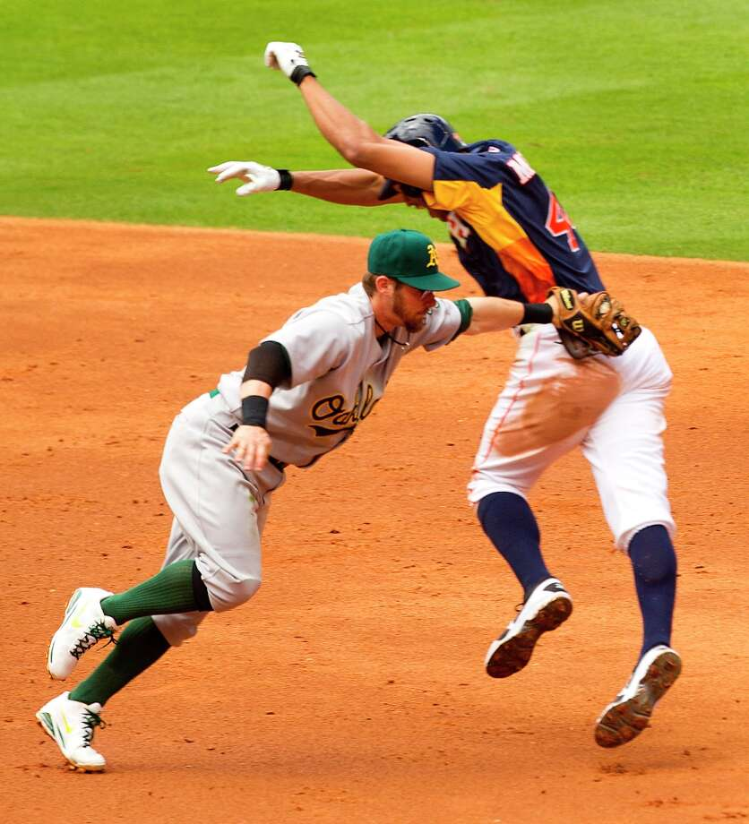 Athletics shortstop Eric Sogard (28) slaps a tag on Astros center fielder Justin Maxwell (44) for an out during the fourth inning. Maxwell was trying to advance to second base after an overthrow at first. Photo: Brett Coomer / © 2013 Houston Chronicle