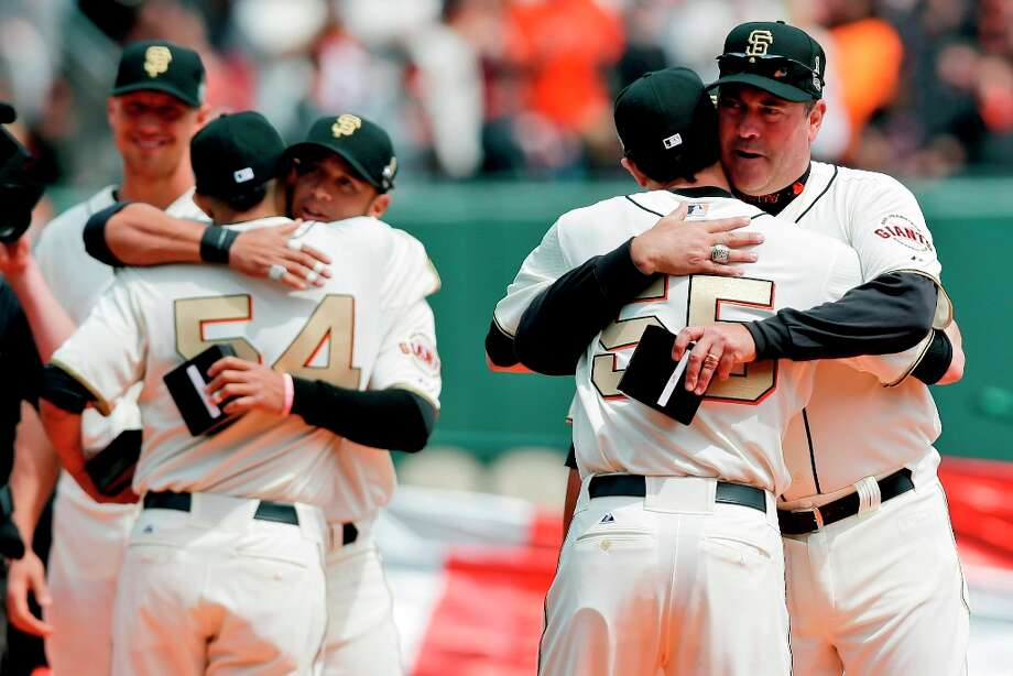 San Francisco Giants relief pitcher Sergio Romo (54) hugs Gregor Blanco as starting pitcher Tim Lincecum (55) hugs special assistant Will Clark during a ceremony awarding the team their 2012 World Series championship rings before a baseball game against the St. Louis Cardinals, Sunday, April 7, 2013, in San Francisco. (AP Photo/Marcio Jose Sanchez) Photo: Marcio Jose Sanchez, Associated Press / AP
