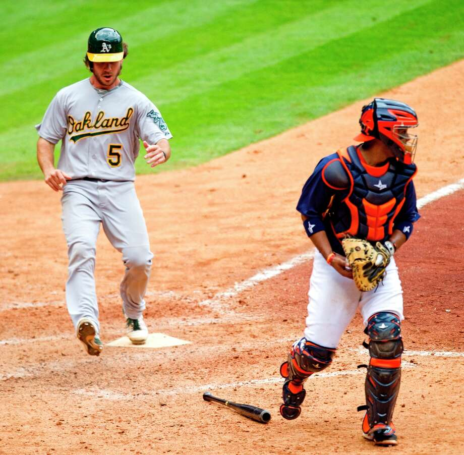 Athletics catcher John Jaso scores on a single by Brandon Moss as Astros catcher Carlos Corporan picks up the throw to home during the ninth inning. Photo: Brett Coomer / © 2013 Houston Chronicle