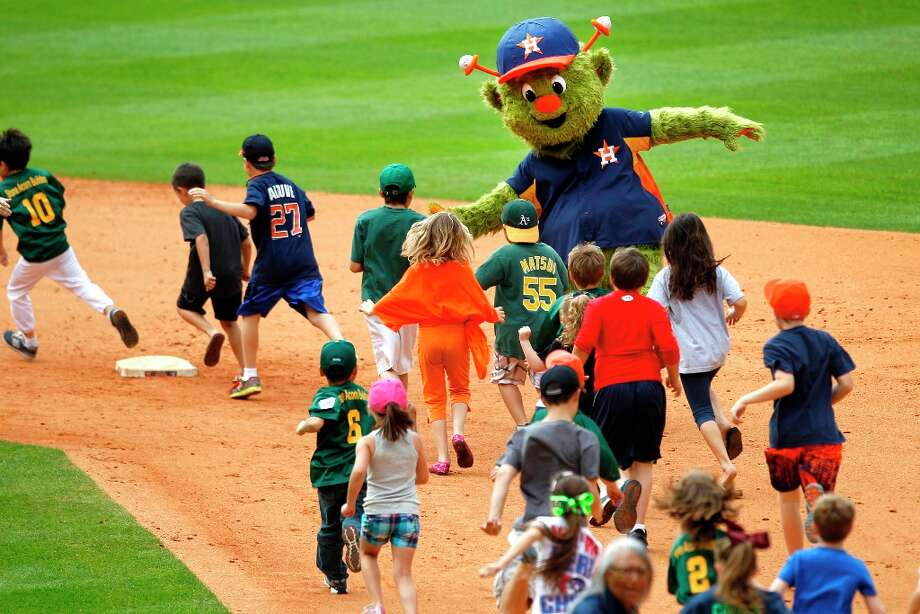 Astros mascot Orbit high-fives kids as they run the bases following the game. Photo: Brett Coomer, Chronicle / © 2013 Houston Chronicle
