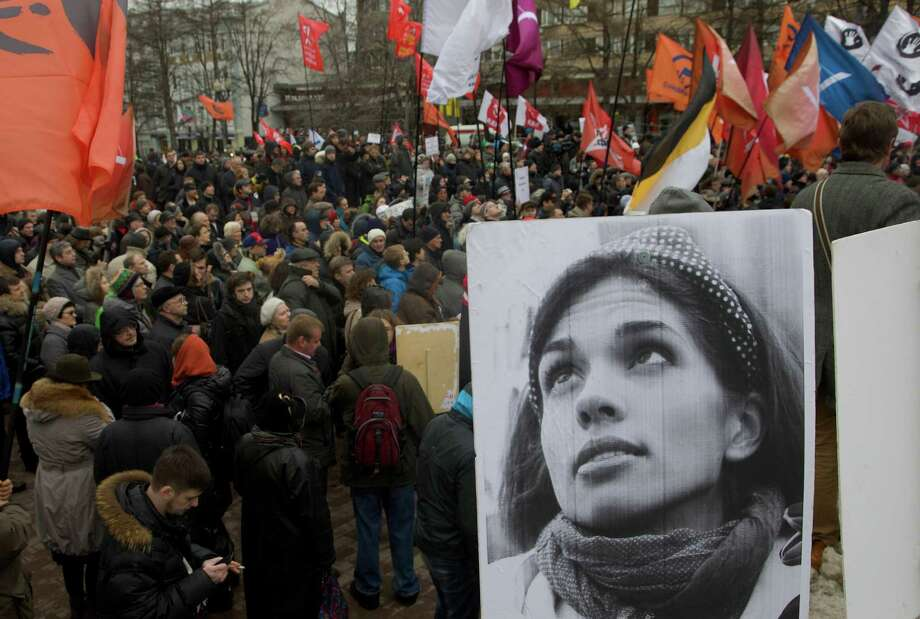 Demonstrators hold flags and a portrait, front, of jailed punk band Pussy Riot member Nadezhda Tolokonnikova, during an opposition rally in Moscow, Saturday, April 6, 2013. Several hundred protesters rallied in central Moscow demanding the release of opposition activists arrested in a massive  protest rally last May. Photo: AP