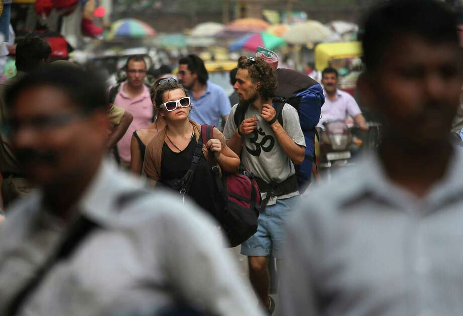 In this Tuesday, April 2, 2013 photo, foreign tourists look for a hotel near the railway station in New Delhi, India. Violence against women, and the huge publicity generated by recent attacks here, is threatening India's $17.7 billion tourism industry. A new study shows tourism has plunged, especially among women, since a 23-year-old Indian student was raped on a New Delhi bus and later died from her injuries, a case that garnered worldwide publicity. Photo: AP