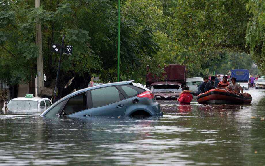 Rescue workers in a raft maneuver through a flooded street where cars are submerged along a street in La Plata, in Argentina's Buenos Aires province, Wednesday, April 3, 2013. At least 35 people were killed by flooding overnight in Argentina's Buenos Aires province, the governor said Wednesday, bringing the overall death toll from days of torrential rains to at least 41 and leaving large stretches of the provincial capital under water. Photo: AP