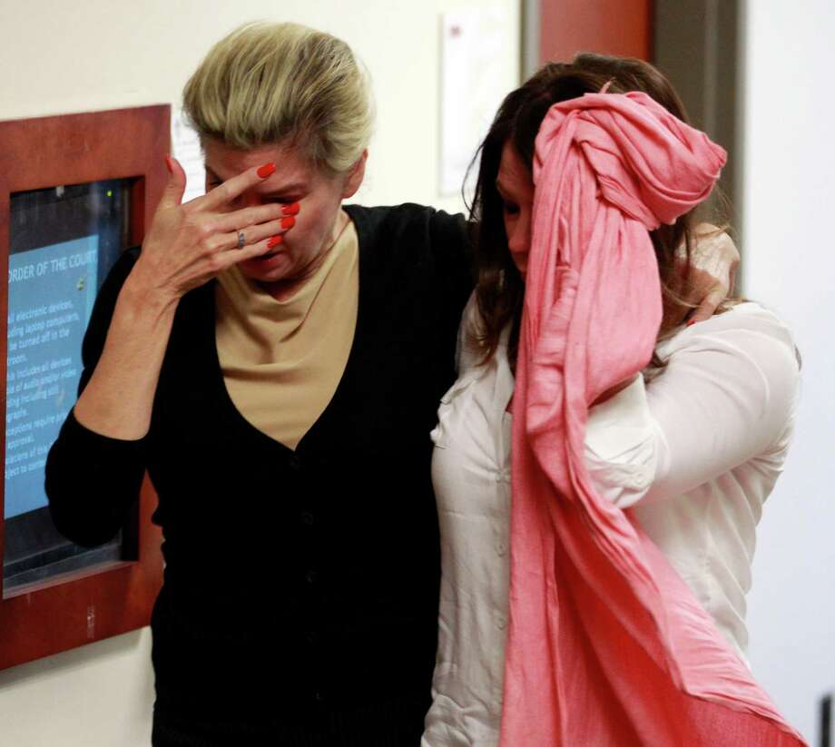 Two unidentified women hide their faces as they leave the courtroom  in the case of  Aurora theater shooting suspect James Holmes in Centennial, Colo., on Monday, April 1, 2013, after hearing that the prosecution will seek the death penalty in the case against Holmes. Photo: AP