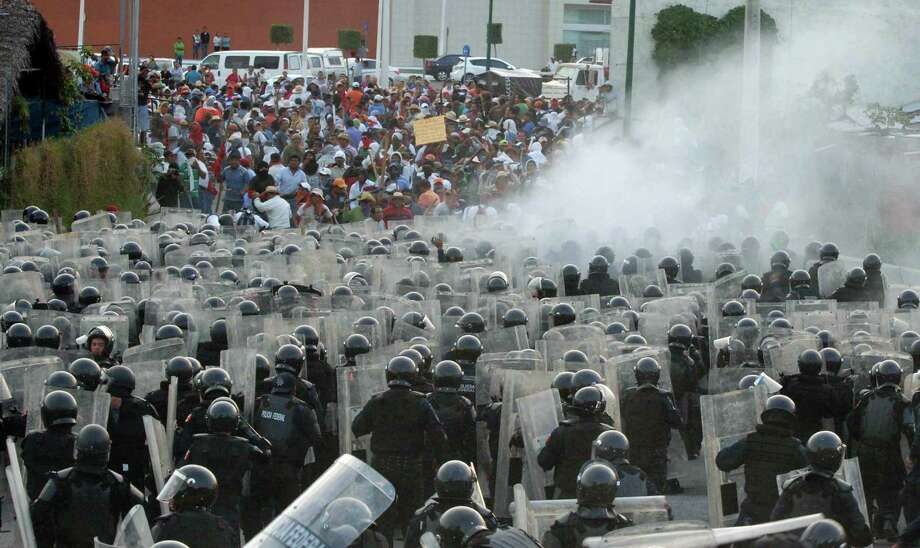 Public school teachers, above, clash with Mexico's Federal Police after they blocked a highway that connects Mexico City with Acapulco in Chilpancingo, Mexico, Friday, April 5, 2013. Radical Mexican public school teachers are holding marches and blocking roads to battle a newly enacted education reform that would weaken union powers. Photo: AP