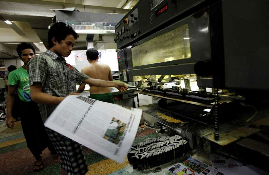 A print worker holds a page of a daily newspaper at a printing press Monday, April 1, 2013, in Yangon, Myanmar. For most people in Myanmar, it will be a novelty when privately run daily newspapers hit the streets on Monday. Many weren't even born when the late dictator Ne Win imposed a state monopoly on the daily press in the 1960s. Photo: AP