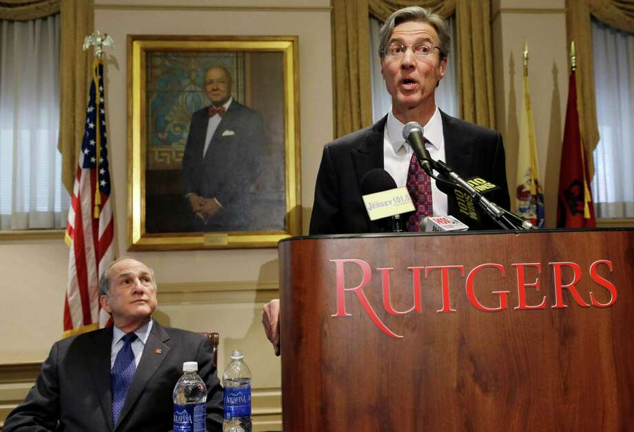 "Rutgers University President Robert Barchi, left, listens as Rutgers University Board of Governors Chair Ralph Izzo, addresses the media Friday, April 5, 2013, in New Brunswick, N.J., after  Barchi announced the resignation of Rutgers athletic director Tim Pernetti, who had decided to ""rehabilitate"" rather than fire the coach whose abusive behavior was captured on a video. That former Rutgers University basketball head coach, Mike Rice was fired Wednesday. University president Barchi's job appeared to be safe after getting a public nod of support from the school's board of governors. Photo: AP"