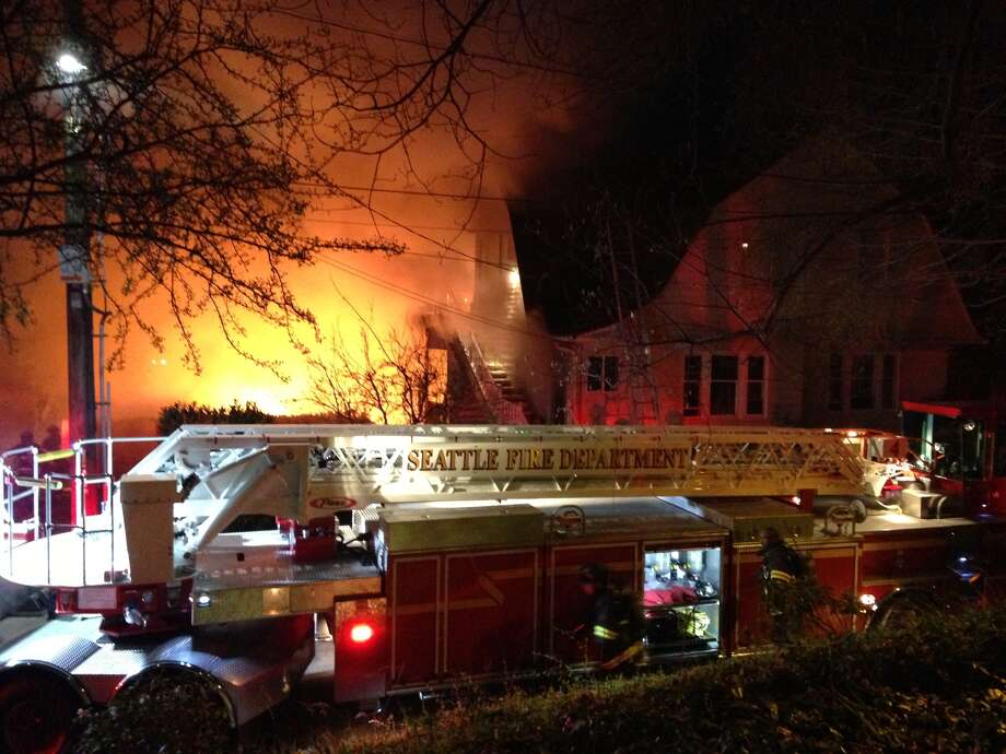 This image provided by Joy Lynch shows Seattle firefighters battling a dramatic blaze that started Monday night April 1, 2013 in one house in the city's Queen Anne neighborhood that quickly spread to two neighboring homes. No serious injuries were reported. Photo: AP