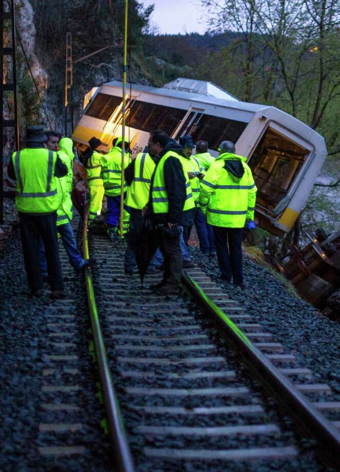 Railway workers are seen next to a derailed train carriage near Golbardo, Spain, Friday, April 5, 2013.  Spanish authorities say a rockfall derailed the train, injuring 11 passengers after the first carriage partially plunged into a river just west of the northern city of Santander. Photo: AP
