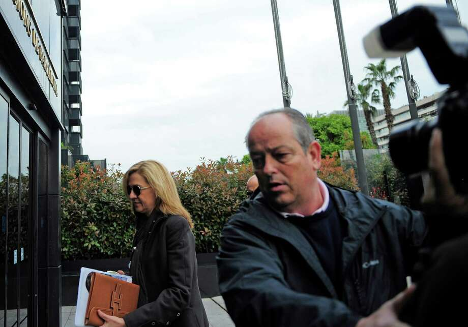 "Spain's Princess Cristina walks toward her office in Barcelona, Spain, as a bodyguard tries to block a photographer, right, Friday, April 5, 2013. Spain's foreign minister said Thursday there was ""enormous concern"" within the government over the naming of one of the king's daughters as a suspect in a corruption case. A Spanish court has named the king's daughter Princess Cristina Wednesday April 3, 2013, as a suspect in an alleged corruption case involving her husband, and the court has announced that it will call her for questioning. Photo: AP"