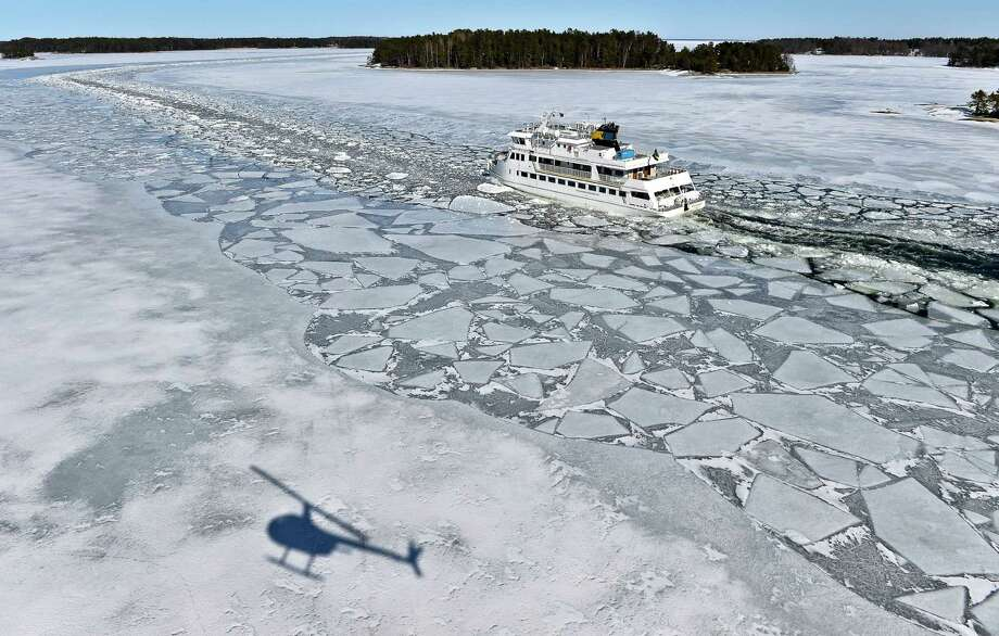 A helicopter casts a shadow on the ice as the passenger ship 'Soderarm' heads Friday morning April 5, 2013, in a channel through the ice made by an icebreaker, for the daily tour to the island Husaro in the Stockholm archipelago in Sweden. According to Swedish Metereological and Hydrological Institute (SMHI), the ice coverage in the Baltic is the thickest and most extensive ever on record. (AP photo / Scanpix Sweden / Anders Wiklund) Photo: AP