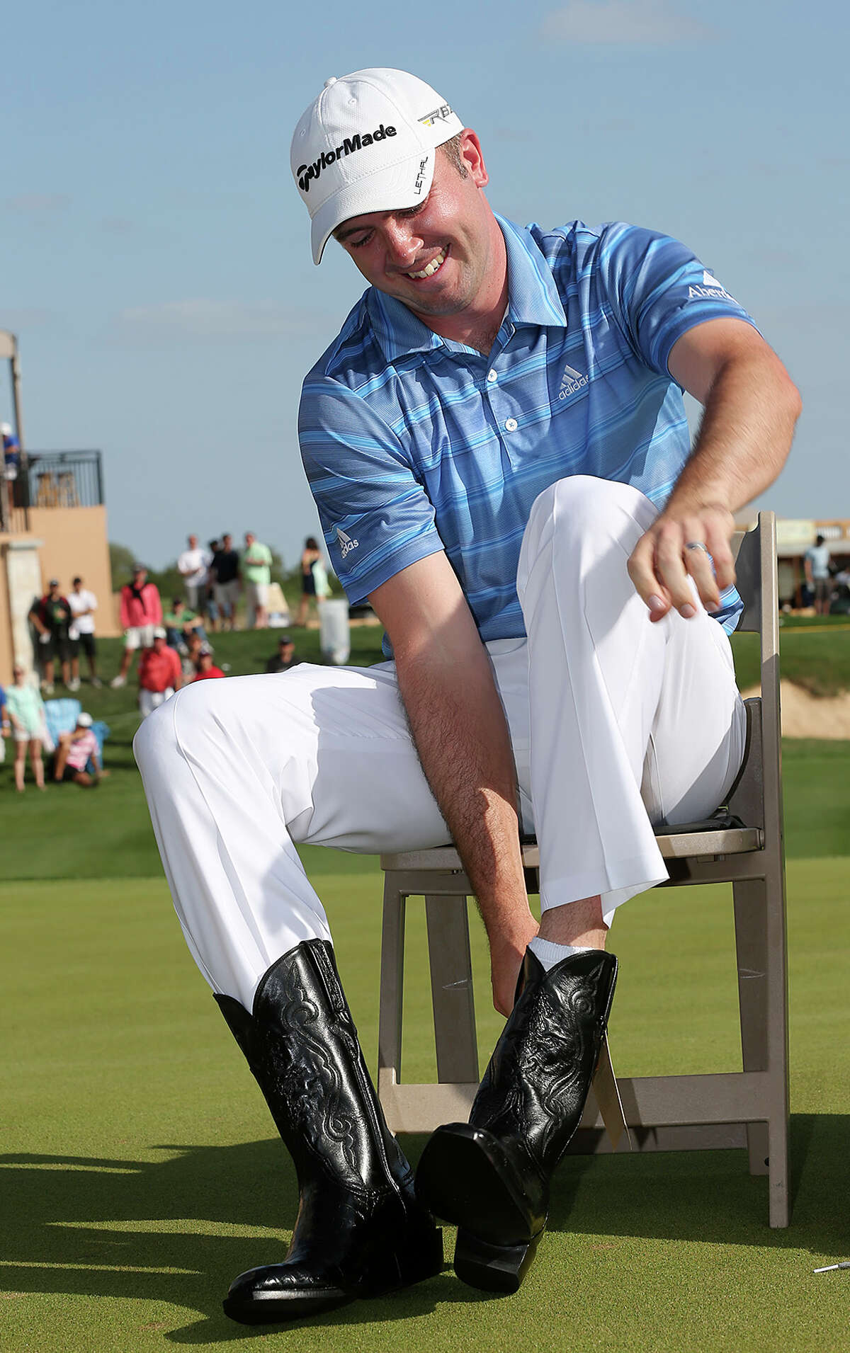 The 2013 Valero Texas Open Champion Martin Laird, of Glasgow, Scotland, puts on cowboy boots that were part of prize after winning the tournament, Sunday, April 7, 2013. Laird also took home $1,116,000.
