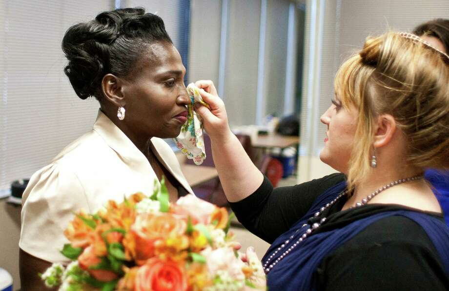 Wanda Ware, left, has her make up fixed by Erika Brunson, before her wedding, Sunday, April 7, 2013, in Houston. Ware, who was homeless for about a year, married Bryan Prejan, who was also homeless. The couple married at Houston's First Baptist's downtown campus, where they attend church. Brunson and other community members donated make up, food and a cake for the wedding. Photo: Nick De La Torre, Chronicle / © 2013 Houston Chronicle