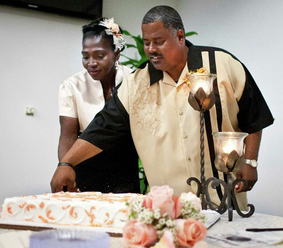 Wanda Ware, and her new husband Bryan Prejean cut their wedding cake in Houston's First Baptists downtown campus Sunday, April 7, 2013, in Houston. The couple were once homeless and attended bible class at the church. Community members donated make up, food and a cake for the wedding. Photo: Nick De La Torre, Chronicle / © 2013 Houston Chronicle
