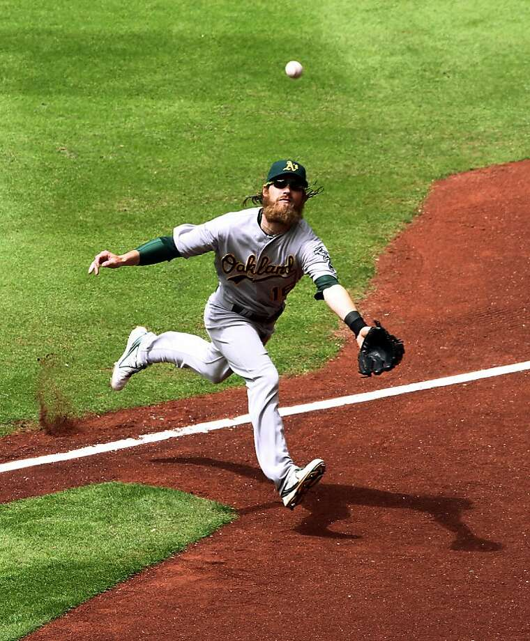 Oakland Athletics outfielder Josh Reddick reaches for a fly ball during the fifth inning of a baseball game against the Houston Astros at Minute Maid Park, Sunday, April 7, 2013, in Houston. (AP Photo/Conroe Courier, Jason Fochtman) Photo: Jason Fochtman, Associated Press