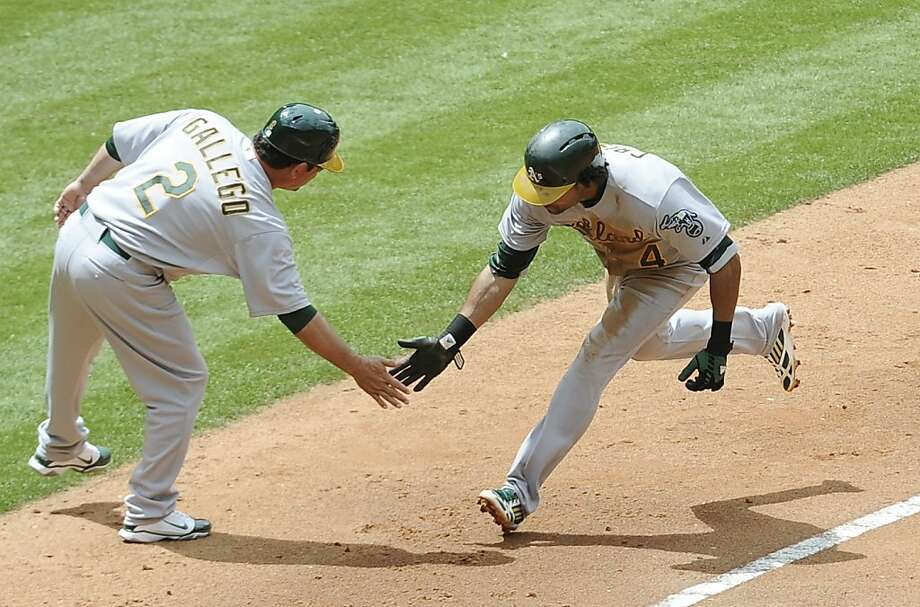 Oakland Athletics third base coach Mike Gallego (2) low-fives Coco Crisp (4) who hit a solo home run against the Houston Astros in the fifth inning of a baseball game on Sunday, April 7, 2013, in Houston. (AP Photo/Pat Sullivan) Photo: Pat Sullivan, Associated Press