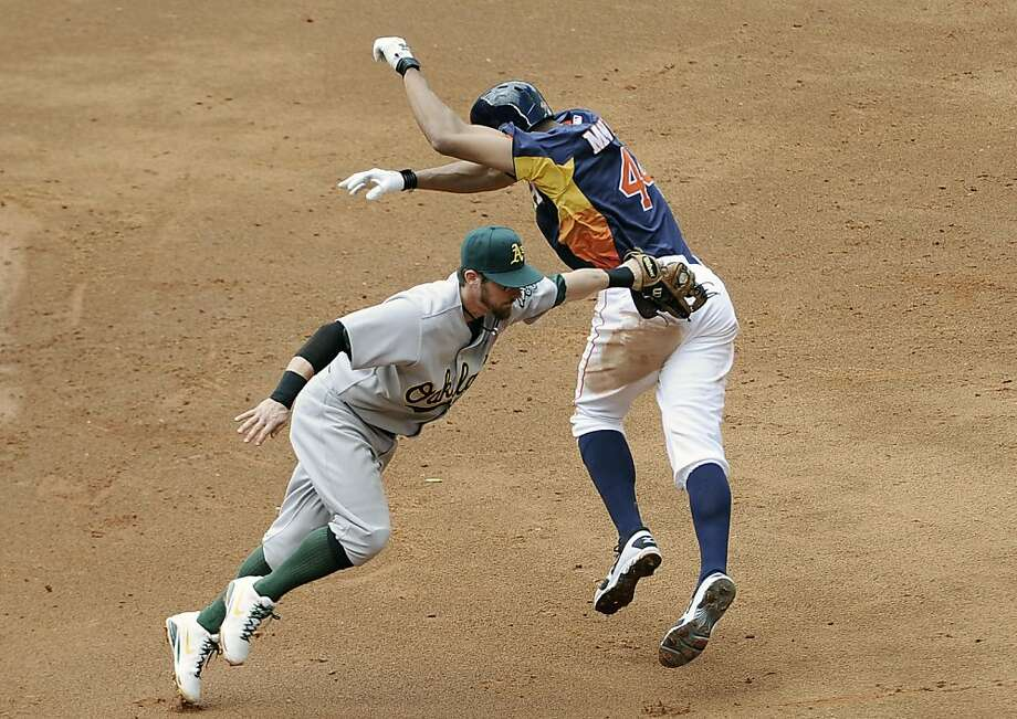Oakland Athletics shortstop Eric Sogard, left, tags out Houston Astros' Justin Maxwell between first and second base in the third inning of a baseball game Sunday April 7, 2013, in Houston. (AP Photo/Pat Sullivan) Photo: Pat Sullivan, Associated Press