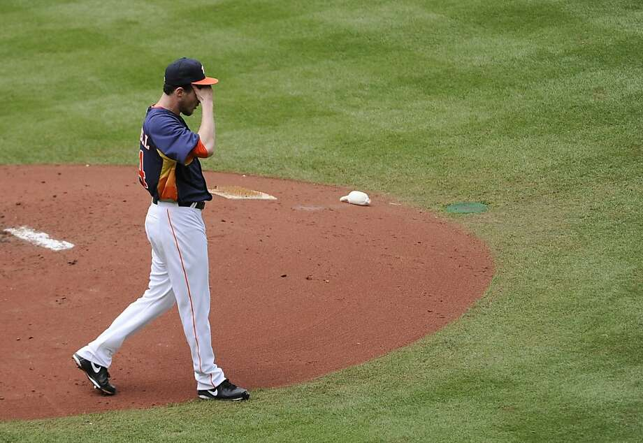 Houston Astros starting pitcher Lucas Harrell takes a moment off the mound to wipe his head in the third inning of a baseball game against the Oakland Athletics Sunday, April 7, 2013, in Houston. (AP Photo/Pat Sullivan) Photo: Pat Sullivan, Associated Press