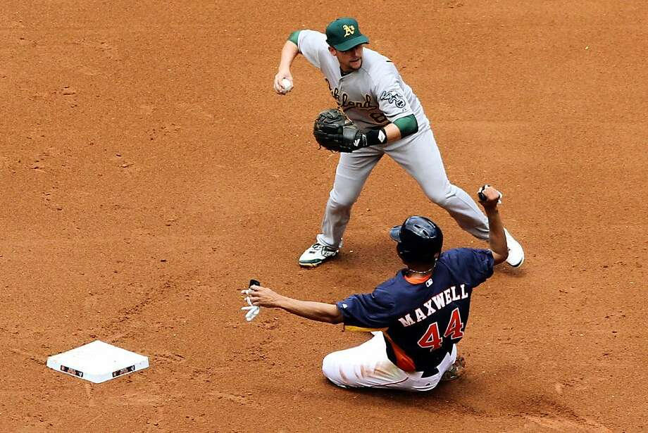 Oakland Athletics shortstop Jed Lowrie (8) turns a double play as Houston Astros' Justin Maxwell (44) slides into second base during the first inning of a baseball game against the Houston Astros at Minute Maid Park, Sunday, April 7, 2013, in Houston. (AP Photo/Conroe Courier, Jason Fochtman) Photo: Jason Fochtman, Associated Press